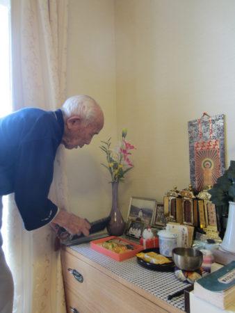 仏様にお水とお茶をあげ、手を合わせる