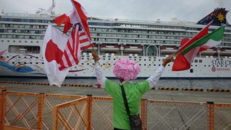 両手に様々な国旗を振りながら、船に向かって中国語で呼びかけています。