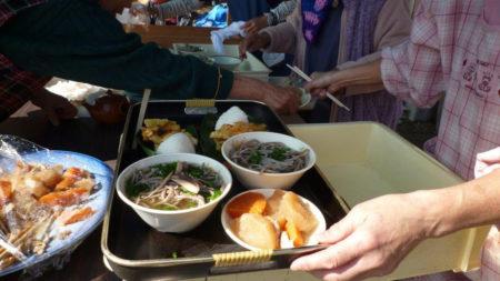 手打ちそばや煮しめ、がねやおにぎりがふるまわれ、焼酎を飲みながら、カラオケ大会で盛り上がっています。