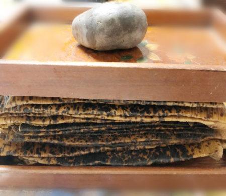 たたんだ竹の皮を重ねて重石をして、しっかり折り目がつくようにする