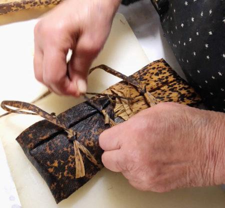 竹の皮を裂いて作ったひもで緩めに結ぶ※茹であがってから結びなおすので、紐は切らないで長いままにしておく。