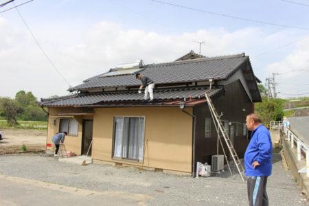 屋根にペンキを塗る作業