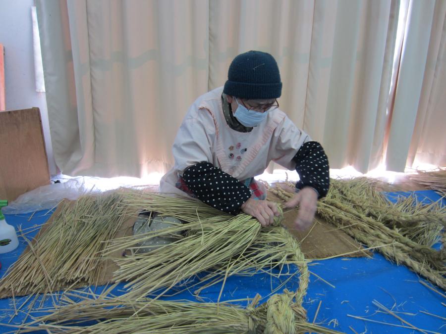編み上がったしめ縄を巻いていく作業